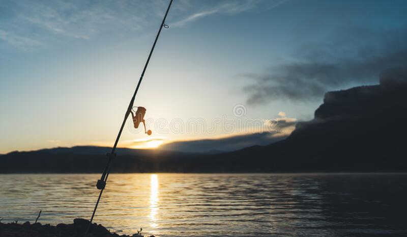 Fishery concept, outline fishing rod at sunrise sunlight, hobby sport on mist evening lake, catch fish on river on background nigh. T sky foggy mount stock photography