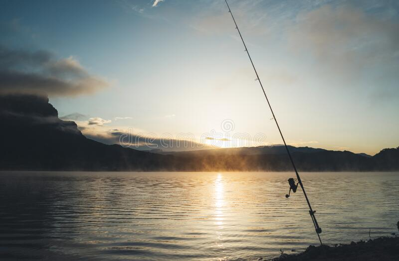 Fishery relax concept, outline fishing rod at sunrise sunlight, hobby sport on mist evening lake, catch fish. On river on background night sky foggy mount stock photo