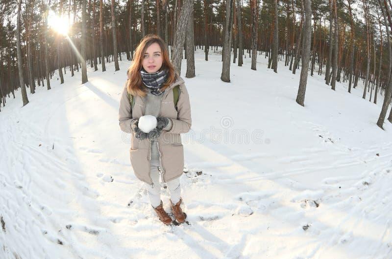 一件棕色外套的一个年轻和快乐的白种人女孩在一个积雪的森林里拿着一个雪球在冬天 Fisheye?? 免版税库存图片