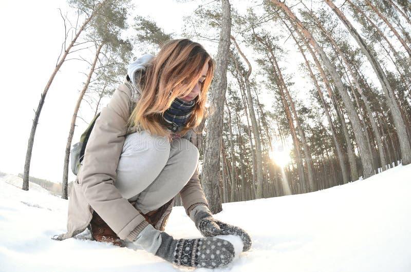 一件棕色外套的一个年轻和快乐的白种人女孩在一个积雪的森林里雕刻一个雪球在冬天 与雪的比赛在 免版税图库摄影