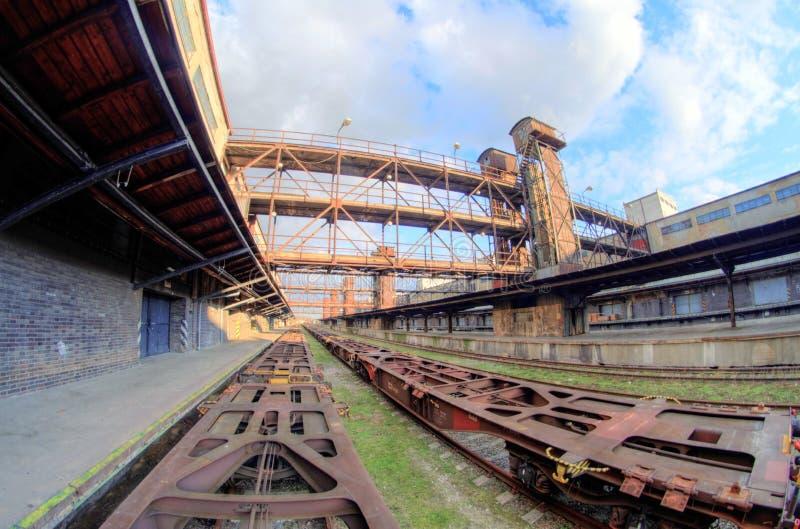 Fisheye bred sikt av vagnar och konstruktioner i gammal övergiven industriell järnvägsstation i Prague royaltyfri foto