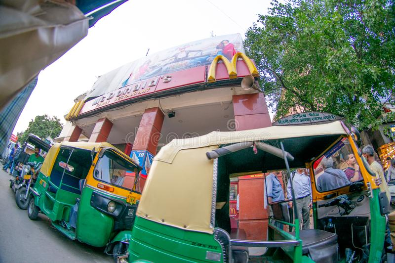 fisheye shot of chandni chowk with auto and electric rickshaw and fast food joint stock images