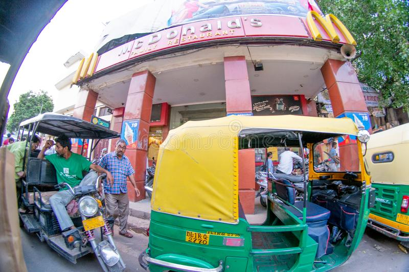 fisheye shot of chandni chowk with auto and electric rickshaw and fast food joint stock photography