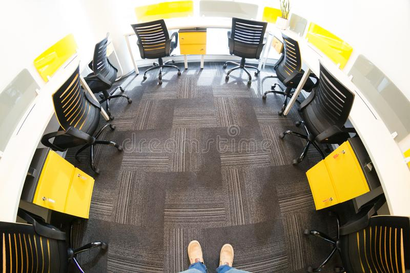 Fisheye shot of office with grey carpet and yellow and black chairs stock photo