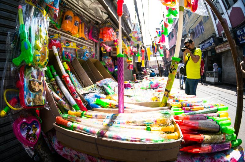 Fisheye shot of a vendor selling holi supplies like water guns and colors stock photos
