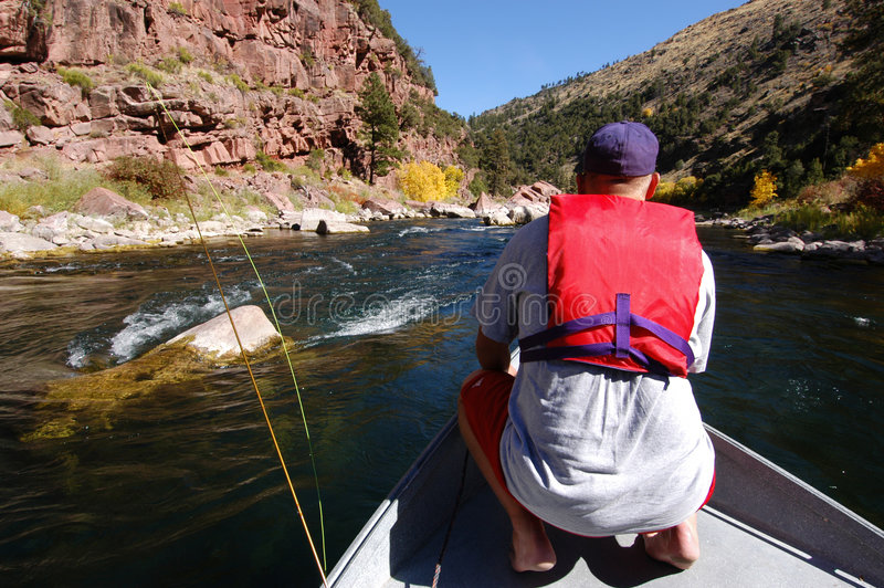 Fishing. Fly fisher on a boat navigating the Green River, Utah royalty free stock image