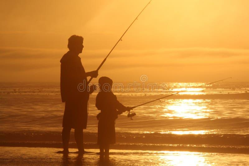 Fishing. Father and son fishing at seashore