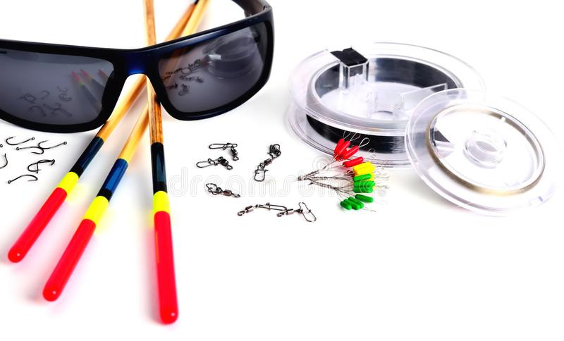 Fishing accessories, blue glasses, floats and fishing line in the reel, stopper hooks and swivels with clasps on a white. Background, close-up, space for stock image