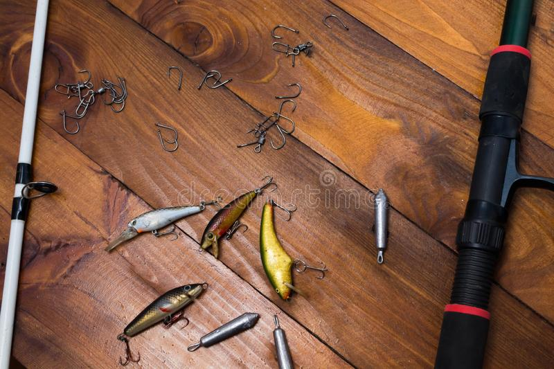 Fishing accessories. On a wooden background, tackle, bait, gear, equipment, hobby, wobbler, spinning, rod, line, lure, metal, reel, tool, sport, hook, spool stock images