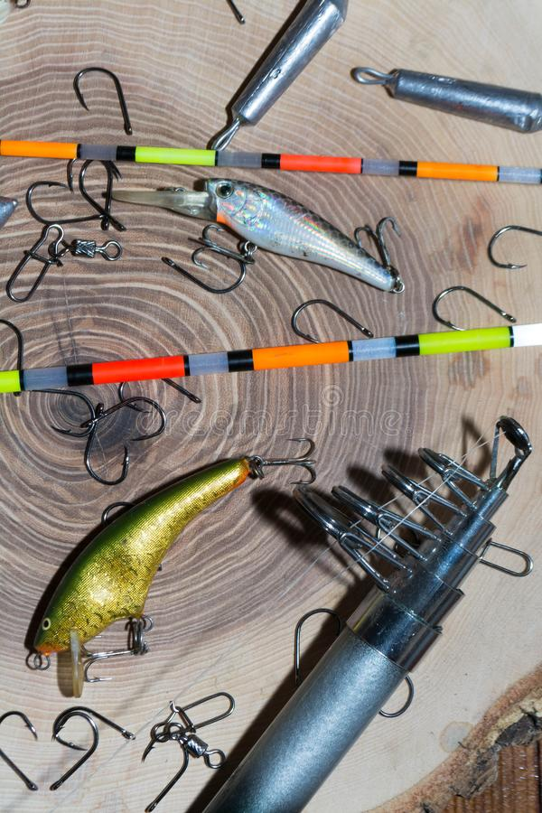 Fishing accessories. On a wooden background, tackle, bait, gear, equipment, hobby, wobbler, spinning, rod, line, lure, metal, reel, tool, sport, hook, spool royalty free stock image