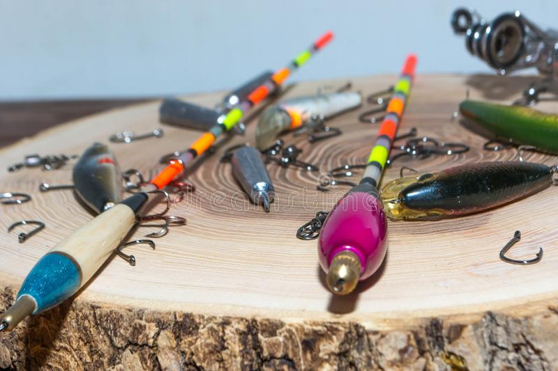 Fishing accessories. On a wooden background, tackle, bait, gear, equipment, hobby, wobbler, spinning, rod, line, lure, metal, reel, tool, sport, hook, spool stock photo