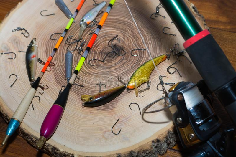 Fishing accessories. On a wooden background, tackle, bait, gear, equipment, hobby, wobbler, spinning, rod, line, lure, metal, reel, tool, sport, hook, spool royalty free stock images