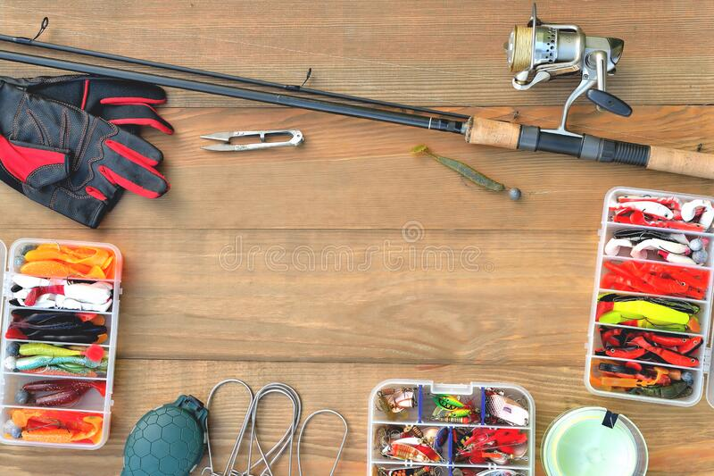 Fishing accessories fishing rod, reel with fishing line, silicone baits and lures, spinning gloves and accessory box on a wooden. Background, close-up, copy royalty free stock photography