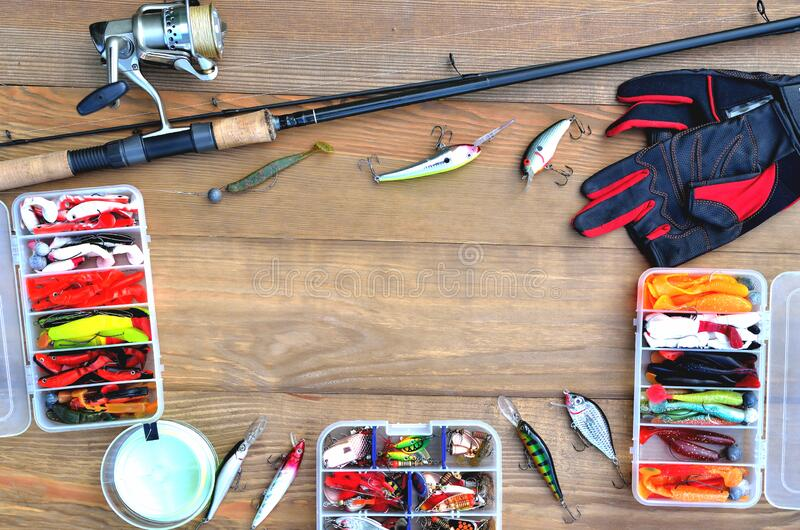 Fishing accessories fishing rod, reel with fishing line, silicone baits and lures, spinning gloves and accessory box on a wooden. Background, close-up, copy stock images
