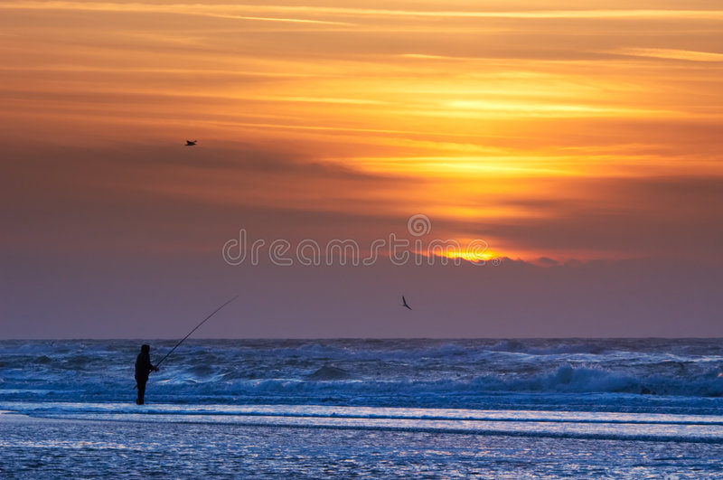 Fishing on the beach stock photography