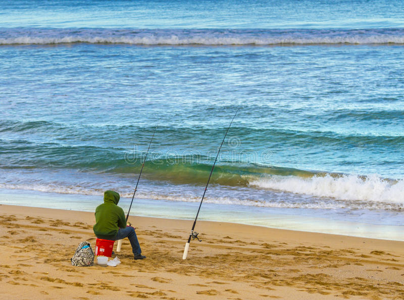 Fishing on a Beach. A man enjoying fishing on a beach with calm blue and green surf gently breaking onto the clean sandy beach royalty free stock photos