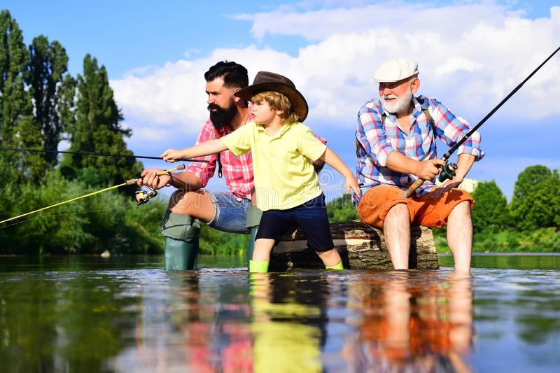 Fishing became a popular recreational activity. Grandfather with son and grandson having fun in river. Men hobby. Family. Fishermen fishing with spinning reel royalty free stock images