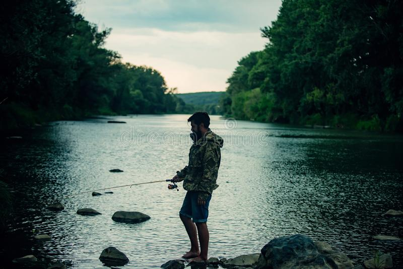 Fishing became a popular recreational activity. Handsome fisherman fishing in a river with a fishing rod. Fishing became a popular recreational activity stock images
