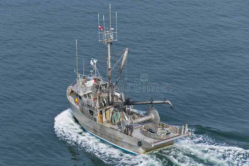 Fishing Boat. A commercial fishing boat heading into the northern Pacific stock photo