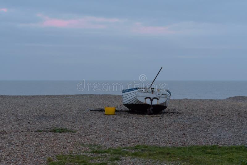 Fishing boat on Aldeburgh shingle beach at sunset. Fishing boat on Aldeburgh, Suffolk shingle beach at sunset stock photos