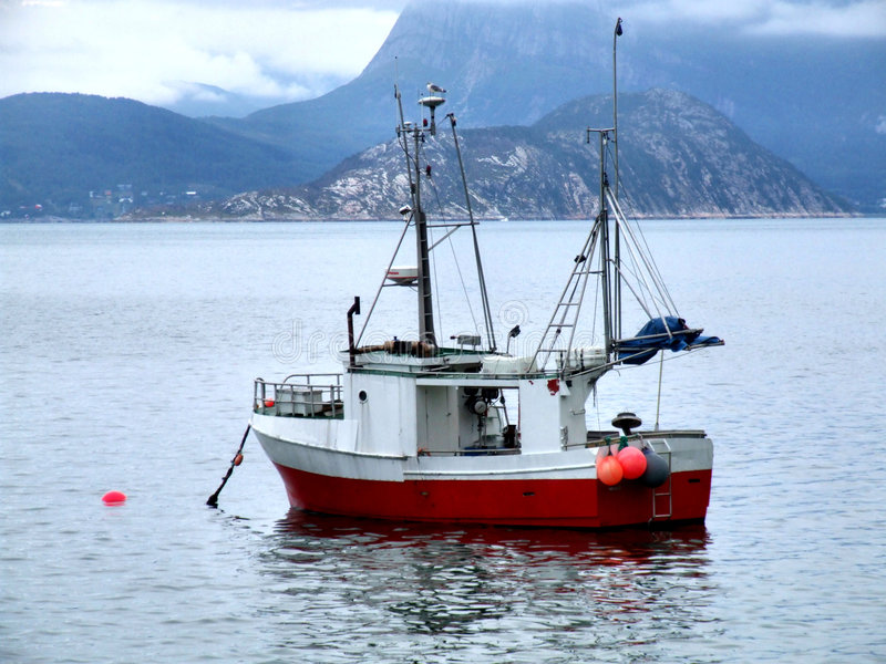 Fishing boat on anchor in haven stock image