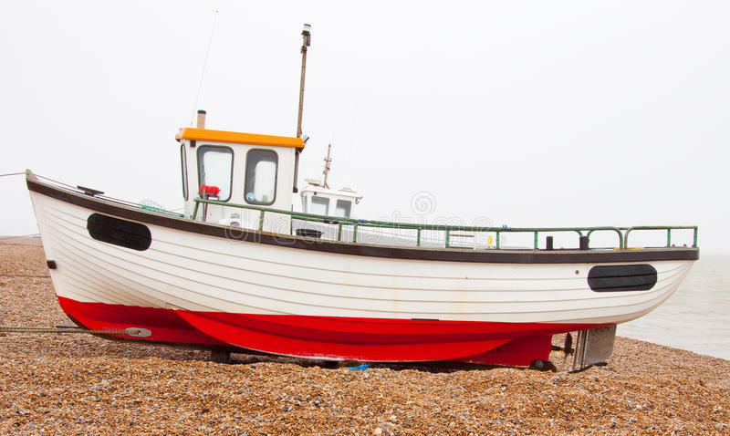 Fishing boat on beach. White and red fishing boat on a shingle beach stock images