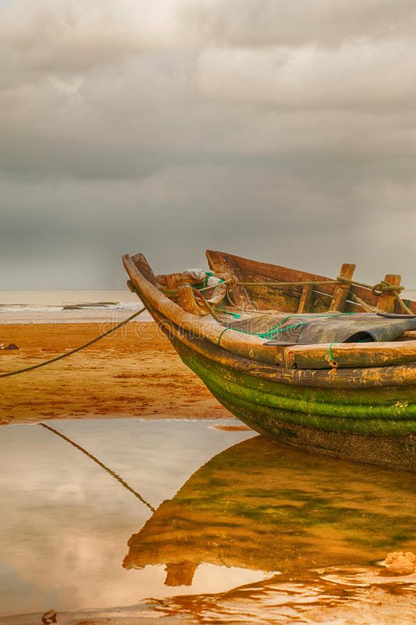 Fishing boat at a beach with cloudy skies stock image