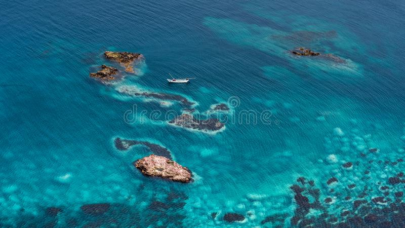 Fishing boat in the colourful sea. Sapporo, Hokkaido, Japan. Fishing boat in the blue sea. Sapporo, Hokkaido, Japan. Beautiful coral reef, near Cape Kamui and royalty free stock images