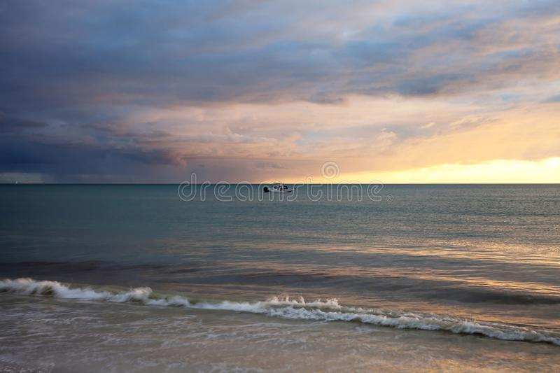 Fishing boat on blue water with rain coming up behind from Marco Island. Florida stock photos