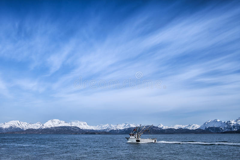 Fishing boat with cloud patterns royalty free stock photos