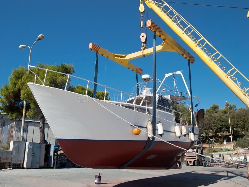 Fishing boat on crane stock photography