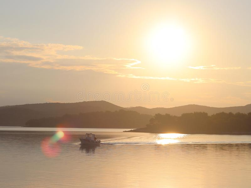 A fishing boat crosses the sea bay in the morning sun. Dawn at the resort. Heavy human labor. Calm and rest after sea crossing. Cr. Oatian Riviera on the stock image