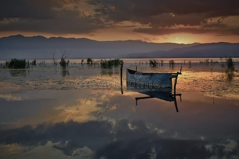 Fishing boat at rising sun royalty free stock photos