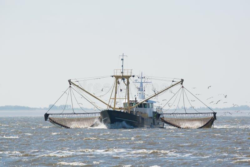 Fishing boat on Dutch wadden sea stock photography