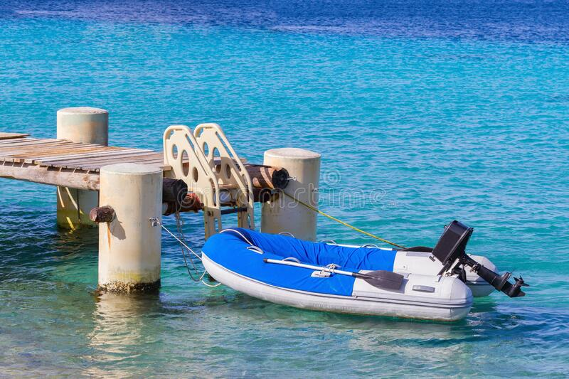 Motorboat is at sea on jetty with stairs royalty free stock photo
