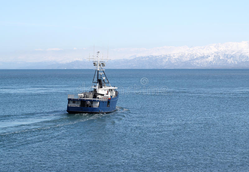 Fishing boat going out to sea stock photos
