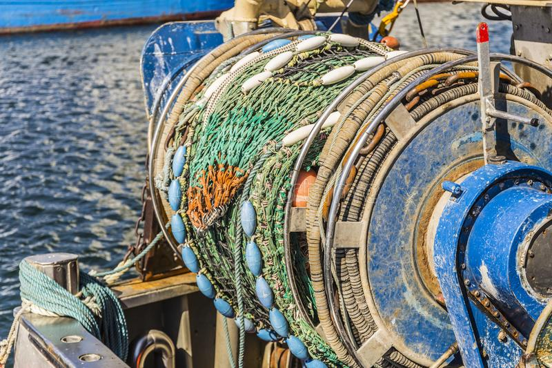 Fishing boat in the harbor - detail shot from fishing net stock photos
