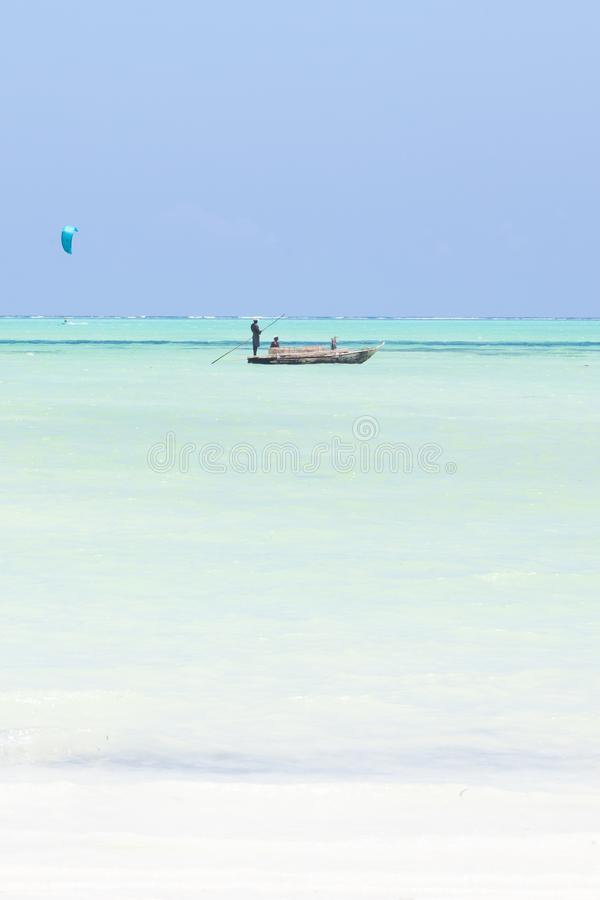 Fishing boat and a kite surfer on picture perfect white sandy beach with turquoise blue sea, Paje, Zanzibar, Tanzania. stock photo