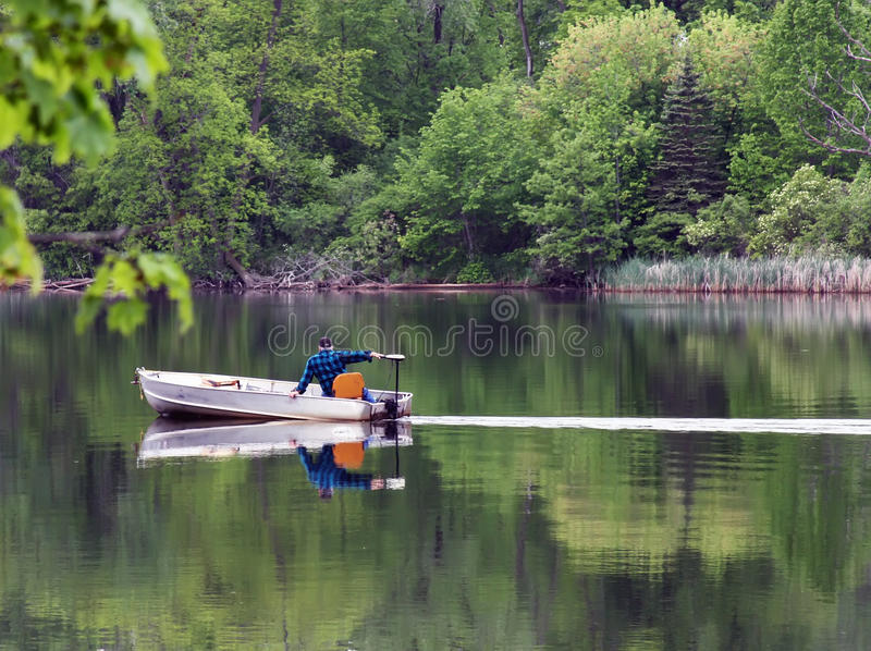 Fishing boat on the lake. Man in aluminum boat crossing a calm lake royalty free stock photos