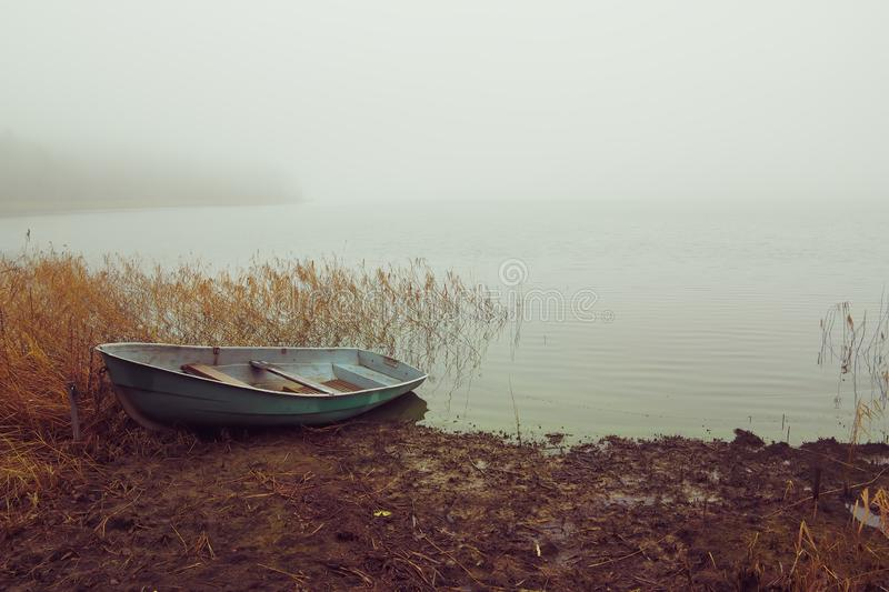 Fishing boat on the lake in the fog stock images