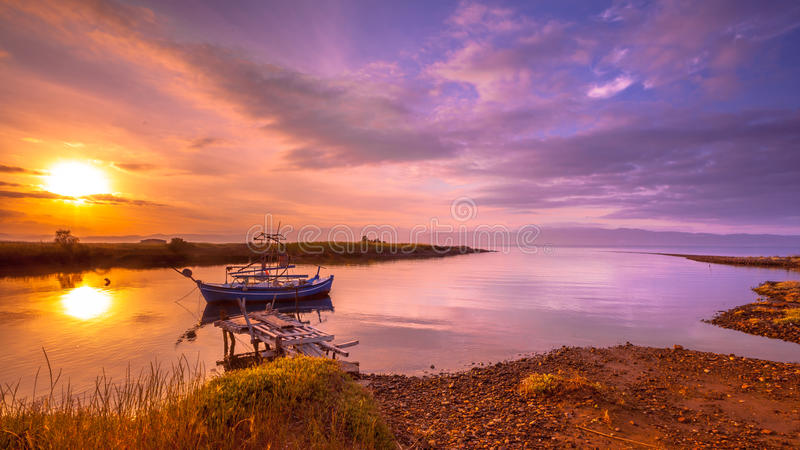 Fishing boat Lesvos. Fishing boat in a river inlet bay during orange sunrise on Lesbos island, Greece stock photo