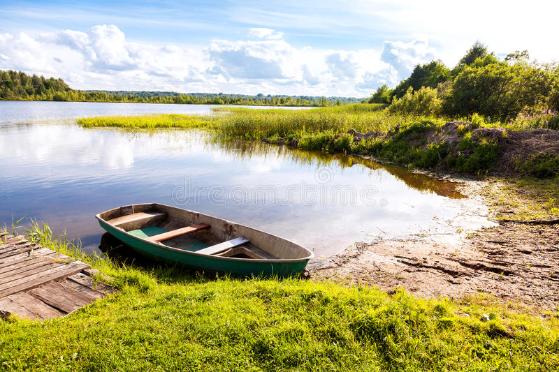 Fishing boat moored on the lake in the morning in summer. Sunny day. Summer's lake scenery. Amazing beautiful landscape day royalty free stock images