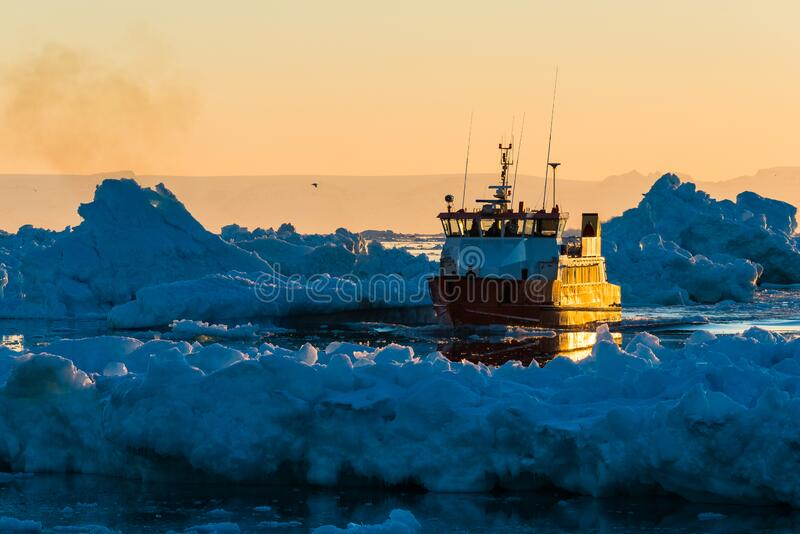 Fishing boat navigates glacier-filled waters at sunset. Ilulissat, Greenland royalty free stock image