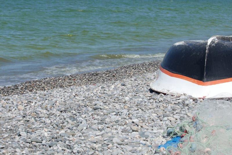 Fishing boat and net lie on the beach, Calis, Fethiye, Turkey. stock photos