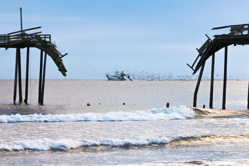 Fishing boat ocean scene Outer Banks OBX NC US. Fish trawler net fishing followed by large flock of seagulls off beach with broken wooden fishing pier structure stock photography