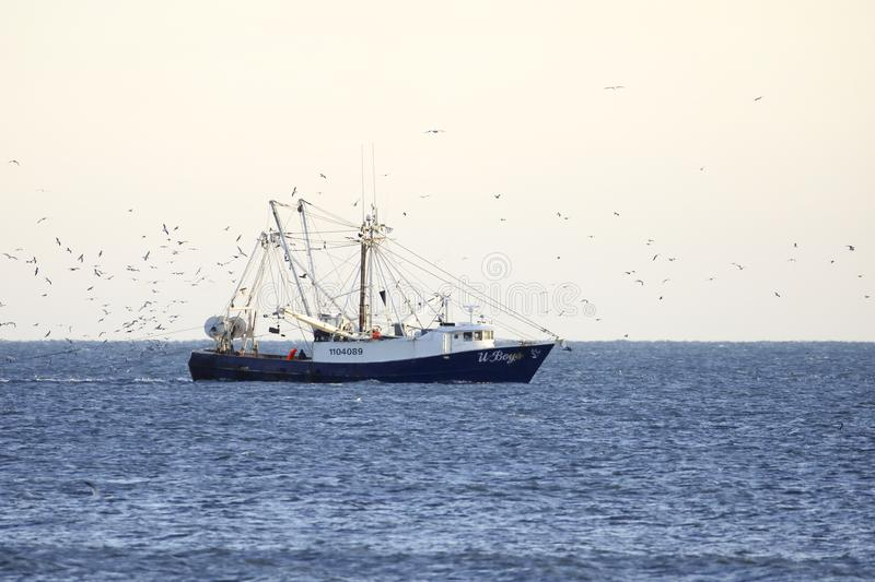 Fishing boat off the shore royalty free stock photography