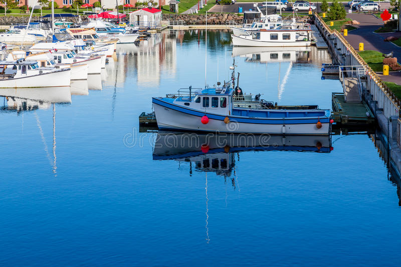 Fishing Boat with Orange Bumper. Small fishing boats in a calm blue harbor on Prince Edward Island in Canada stock photography