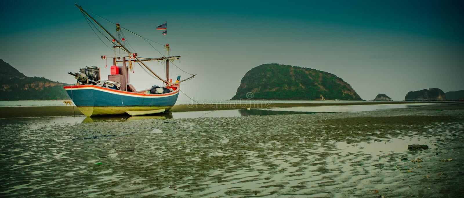 Fishing Boat stop on the coast at the daytime have long beach at Sam Roi Yot beach Prachuap Khiri Khan beautiful ocean in Thailand. Fishing Boat are painted with stock photos