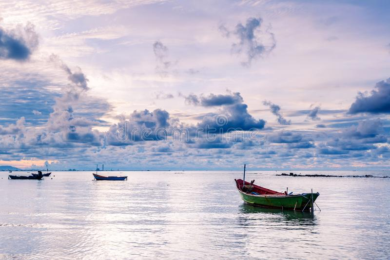 Fishing boat in perfectly calm sea water like glass with the clouds in the sky, long Exposure taken during sunrise. Fishing boat in perfectly calm sea water like royalty free stock image