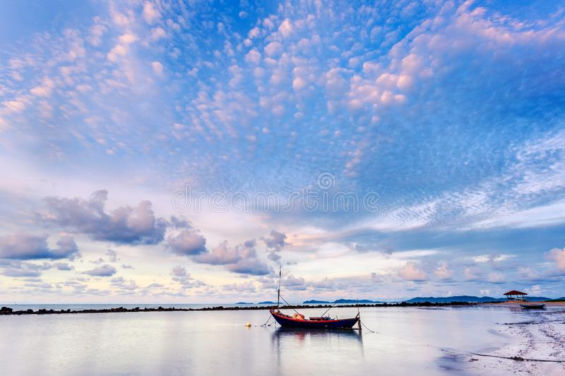 Fishing boat in perfectly calm sea water like glass with the clouds in the sky, long Exposure taken during sunrise. Fishing boat in perfectly calm sea water like royalty free stock photo